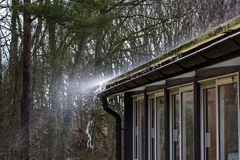 Water splashing down from a roof. stock photo