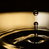 Water splashing. Dropping bubble. Rings waves in dark bronze and black liquid splash. macro view, soft focus, shallow Stock Image