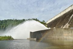 Water splashing from floodgate Khun Dan Prakarn Chon huge concrete dam in Thailand. On sunny day stock photography