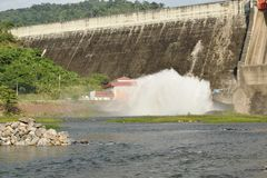 Water splashing from floodgate Khun Dan Prakarn Chon huge concrete dam in Thailand. On sunny day stock photo