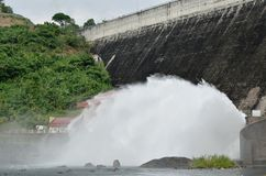Water splashing from floodgate Khun Dan Prakarn Chon huge concrete dam in Thailand. On sunny day royalty free stock photo