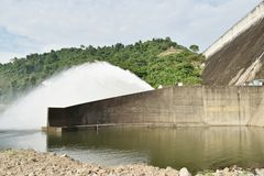 Water splashing from floodgate Khun Dan Prakarn Chon huge concrete dam in Thailand. On sunny day stock image