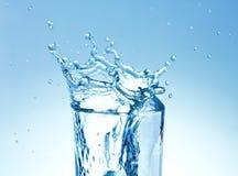 Water splashing in glass. Clear blue water splashing in glass stock photos