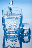 Water splashing into glass with ice cubes. Blue water splashing into glass with ice cubes royalty free stock photography