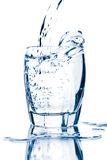 Water splashing into glass isolated. Over white royalty free stock image