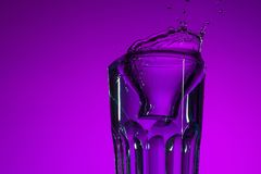The water splashing in glass on lilac background Stock Photo
