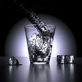 Water splashing in a glass of water (low point of view). 3D render. Water splashing in a glass of water surrounded by ice cubes stock illustration