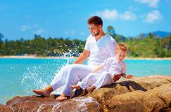 Water splashing on happy father and son on tropical beach Stock Photos