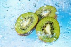 Water splashing on kiwi slices Stock Photo