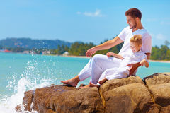 Water splashing on laughing father and son on rocky coast Royalty Free Stock Photography