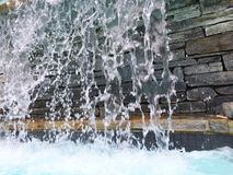 Waterfall. Cascading falling splashing water in a man made pool with natural stone background low angle view Royalty Free Stock Photo