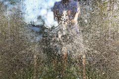 Water splashing out of garden hose. Against window stock images