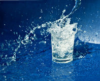 Splashing water from glass. Water splashing out of the glass stock photo