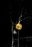 Water splashing out of a glass as an ice cube is dropped in to a Royalty Free Stock Photo