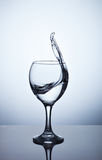 Water splashing out of a tall wine glass. From a tall glass splashes water with a spray Stock Images