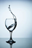 Water splashing out of a tall wine glass. From a tall glass splashes water with a spray Royalty Free Stock Photography