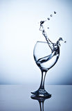 Water splashing out of a tall wine glass. From a tall glass splashes water with a spray Stock Photos