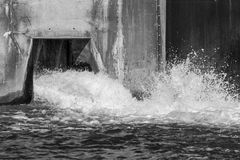 Water splashing and pouring out from a dam overflow concrete culvert. Black and white image with frozen motion stock photos