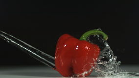 Water splashing on a red pepper stock video footage