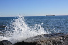 Water Splashing on a rock. Water from lake Superior splashing along the shore with a cargo ship in the background stock image