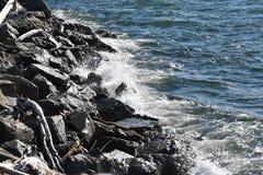 Water splashing on rocky sides. Water splashing rocks on a quiet day stock photography