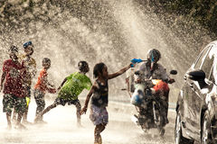 Water Splashing in Songkran Festival. The horizontal image of people / children enjoying water splashing in the artificial water tunnel during Songkran Festival royalty free stock photos