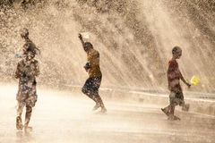 Water Splashing in Songkran Festival. The horizontal image of people / children enjoying water splashing in the artificial water tunnel during Songkran Festival Stock Photo
