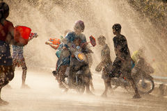 Water Splashing in Songkran Festival. The horizontal image of people / children enjoying water splashing in the artificial water tunnel during Songkran Festival stock image