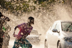 Water Splashing in Songkran Festival. The horizontal image of people / children enjoying water splashing in the artificial water tunnel during Songkran Festival royalty free stock photography