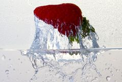 Water splashing on a strawberry. Against a white background stock images