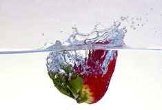 Water splashing on a strawberry. Against a white background royalty free stock photo
