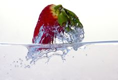 Water splashing on a strawberry. Against a white background royalty free stock photography