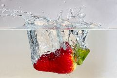 Water splashing on a strawberry. Against a white background royalty free stock images