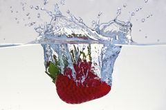 Water splashing on a strawberry. Against a white background royalty free stock photos