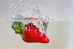 Water splashing on a strawberry. Against a white background royalty free stock image