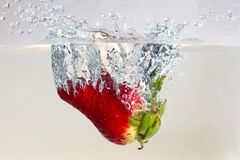 Water splashing on a strawberry. Against a white background stock image