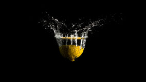 Water splashing from the surface of the liquid. In a spray of droplets as a halved lemon is dropped into the water from above on a dark background with stock image