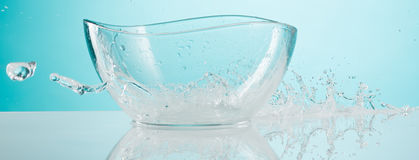 The water splashing to glass bowl on white background Royalty Free Stock Photos