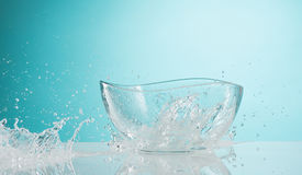 The water splashing to glass bowl on white background. The water splashing inro glass bowl on white background stock images