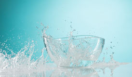 The water splashing to glass bowl on white background. The water splashing inro glass bowl on white background stock photo