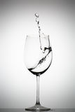 Water splashing in a wine glass. On a gradient background stock image
