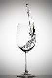 Water splashing in a wine glass. On a gradient background royalty free stock photography