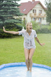 The water splatter. Blond girl in a home garden screaming and try to stop a water splatter against her Stock Photo