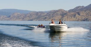 Water sports. Recreational motorboat pulling tubers on a lake Stock Photo