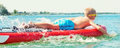 Boy swimming on stand up paddle board.Water sports , active lifestyle. Water sports , active lifestyle.Boy swimming on stand up paddle board stock image