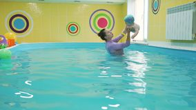 Water sports activity of cute baby boy. Little baby doing water exercises with swimming instructor in slow motion. Prevention of diseases of the musculoskeletal stock video