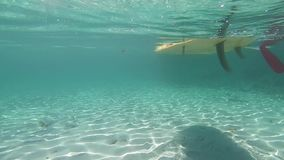 Water sports: slow motion passage of a white stand up paddle board taken from underwater in the crystalline sea with the shadow of. The shape reflected on the stock footage