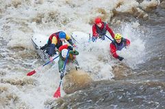 Water sportsmen in threshold. MOSCOW - APR 10: Unidentified sportsmen train in whitewater rafting techniques in Pakhra river during a traditional spring meeting Royalty Free Stock Image