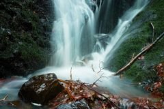 Water spray below small waterfall on mountain stream, water is falling over mossy boulder. The spray create on level and gravel mi Stock Photo