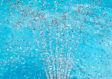 Water spray fountain on turquoise background Stock Images